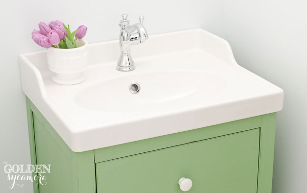 Green bathroom vanity and white vintage looking sink