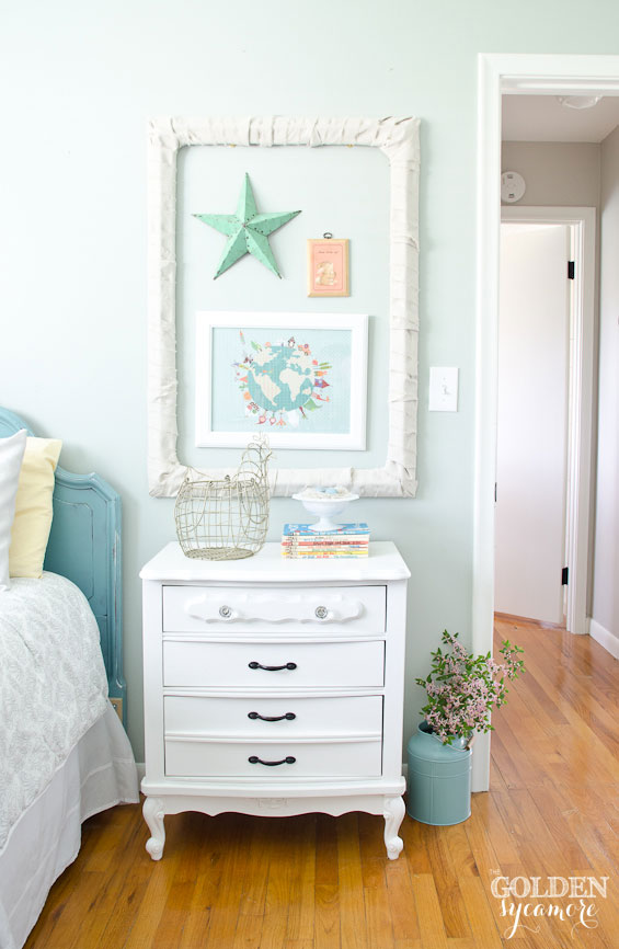 Mini gallery wall and white end table in cottage style little girl's room