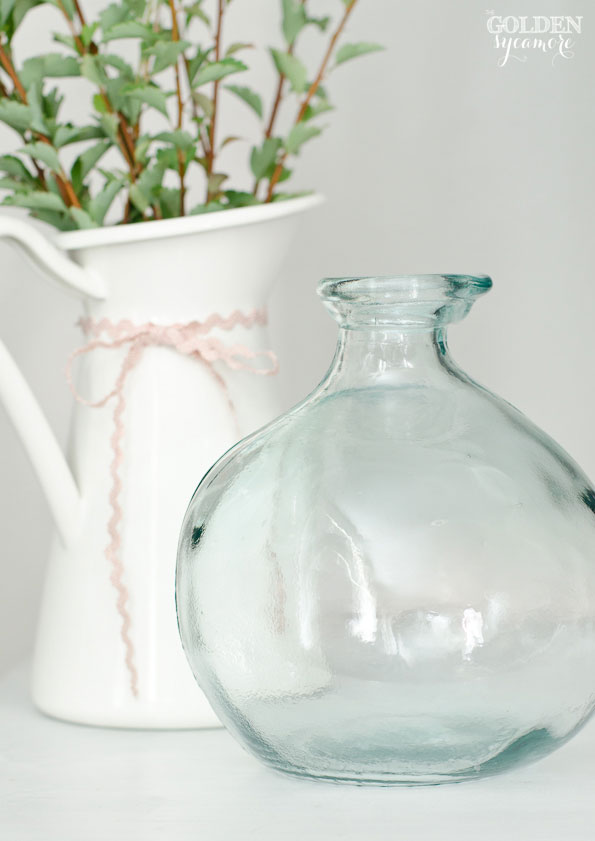 Glass jar and greenery in white pitcher