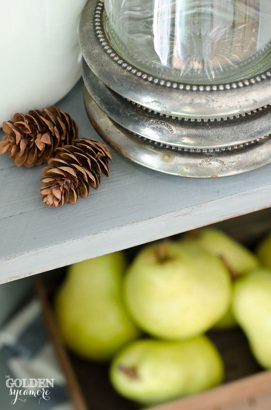 Vintage coasters, pinecones, and pears in painted corner hutch