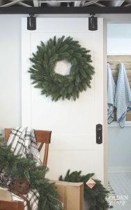 Rustic Christmas decor with gorgeous wreath on sliding barn style door