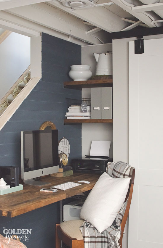 Rustic office with butcher block desk and shelves and sliding barn style door