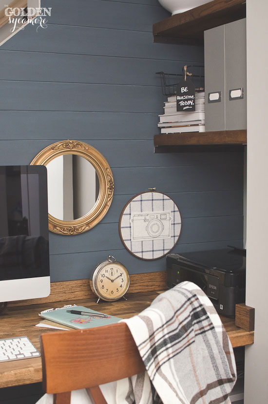Rustic office nook with stained butcher block desk and blue painted plank wall