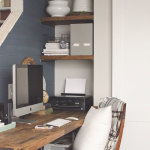 Small office nook tucked next to stairs with butcher block desk and plank wall