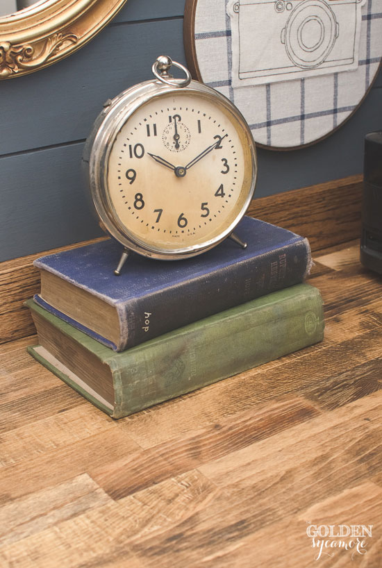 Rustic office nook - vintage clock and books on butcher block desk