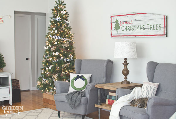 Rustic living room with vintage barn wood Christmas tree sign - thegoldensycamore.com