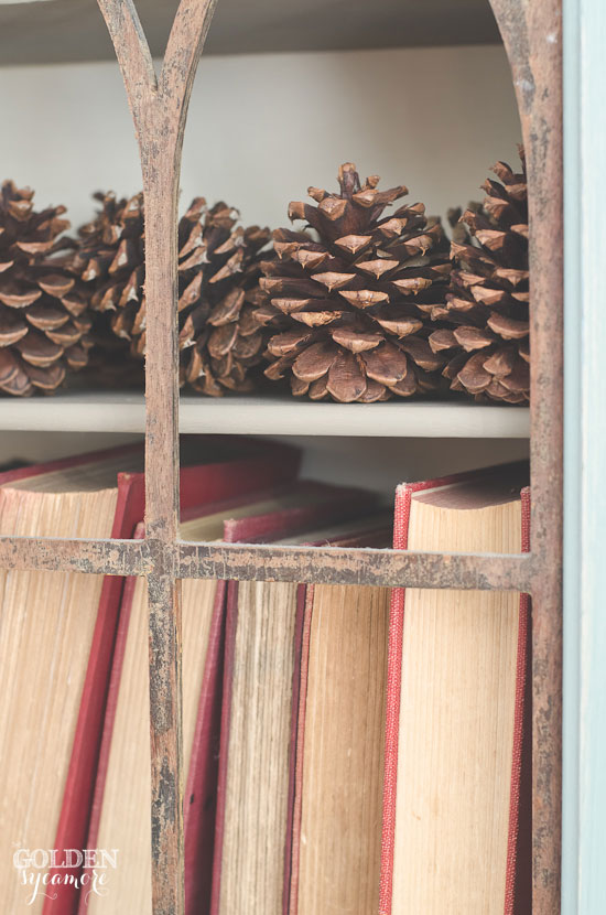Simple Christmas decor with pine cones and vintage books via www.thegoldensycamore.com