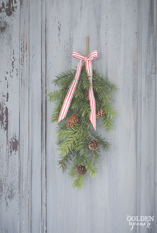 Pine swag with red and white ribbon on old door via www.thegoldensycamore.com