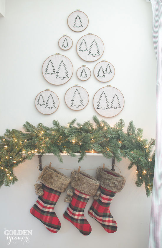 Faux Christmas mantel with stockings, garland, and evergreen tree embroidery hoops